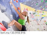 Купить «Woman training at bouldering gym», фото № 33918916, снято 9 июля 2018 г. (c) Яков Филимонов / Фотобанк Лори