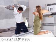 Купить «Couple having pillow fight in bedroom», фото № 33918956, снято 24 сентября 2018 г. (c) Яков Филимонов / Фотобанк Лори