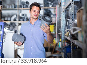 Man is choosing plastic trumpet in plumbing department. Стоковое фото, фотограф Яков Филимонов / Фотобанк Лори