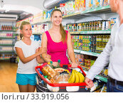 Positive family with teen daughter and purchases in shopping. Стоковое фото, фотограф Яков Филимонов / Фотобанк Лори