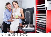 Купить «Positive couple looking at modern kitchen», фото № 33919072, снято 15 июня 2017 г. (c) Яков Филимонов / Фотобанк Лори