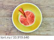 Small ripe cut watermelon on a green plate on a wooden tabletop. Стоковое фото, фотограф Евгений Харитонов / Фотобанк Лори