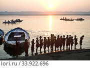 Schoolboys from a 'gurukul' ( hindu school) are praying the rising sun ( the sun is the hindu god Surya) ( Ganges river in Varanasi, India). In the river, boats are carrying tourists. Стоковое фото, фотограф Franck Metois / age Fotostock / Фотобанк Лори
