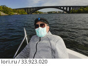 Купить «Stockholm, Sweden An 82 year old man sits in a little boat on a sunny day with a mask duting the Coronavirus pandemic.», фото № 33923020, снято 24 мая 2020 г. (c) age Fotostock / Фотобанк Лори