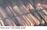 Купить «BBQ.Grilled sausages are fried and smoked in charcoal grills. Sausages in a natural shell. Tasty juicy sausages grilling over a fire,», видеоролик № 33928224, снято 4 июня 2020 г. (c) Куликов Константин / Фотобанк Лори