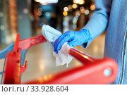 Купить «hand cleaning shopping cart handle with wet wipe», фото № 33928604, снято 30 апреля 2020 г. (c) Syda Productions / Фотобанк Лори