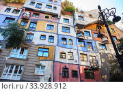 Hundertwasser house in Vienna, Austria. The Hundertwasserhaus apartment block has colorful facade, undulating floors, a roof covered with earth and grass, and large trees (2019 год). Редакционное фото, фотограф Nataliia Zhekova / Фотобанк Лори