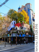 Hundertwasser house in Vienna, Austria. The Hundertwasserhaus apartment block has colorful facade, undulating floors, a roof covered with earth and grass, and large trees growing from inside (2019 год). Редакционное фото, фотограф Nataliia Zhekova / Фотобанк Лори