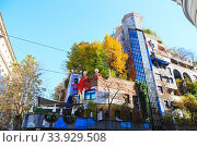 Купить «Hundertwasser house in Vienna, Austria. The Hundertwasserhaus apartment block has colorful facade, undulating floors, a roof covered with earth and grass, and large trees growing from inside», фото № 33929508, снято 27 октября 2019 г. (c) Nataliia Zhekova / Фотобанк Лори