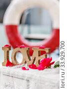 "Купить «Carved wood word ""Love"" among pink rose petals on the background of a life buoy», фото № 33929700, снято 31 мая 2014 г. (c) Nataliia Zhekova / Фотобанк Лори"