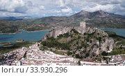 Купить «Picturesque aerial view of Zahara de la Sierra with ancient castle on rocky hill against backdrop of lake, Spain», видеоролик № 33930296, снято 18 апреля 2019 г. (c) Яков Филимонов / Фотобанк Лори