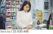 Portrait of chinese female pharmacist is standing with medicines in pharmacy. Стоковое видео, видеограф Яков Филимонов / Фотобанк Лори