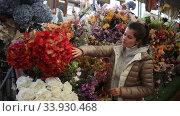 Купить «Portrait of young attractive woman choosing artificial flowers in store», видеоролик № 33930468, снято 17 марта 2020 г. (c) Яков Филимонов / Фотобанк Лори