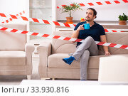 Купить «Young man feeling bored at home in self-isolation concept», фото № 33930816, снято 1 апреля 2020 г. (c) Elnur / Фотобанк Лори