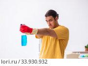 Купить «Young male contractor cleaning the house», фото № 33930932, снято 3 февраля 2020 г. (c) Elnur / Фотобанк Лори