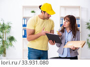 Купить «Young male courier delivering parcel to the office», фото № 33931080, снято 22 ноября 2019 г. (c) Elnur / Фотобанк Лори