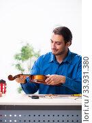 Купить «Young male repairman repairing violin», фото № 33931380, снято 25 октября 2019 г. (c) Elnur / Фотобанк Лори