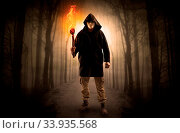 Mysterious man coming from a path in the forest with burning flambeau concept. Стоковое фото, фотограф Zoonar.com/rancz / easy Fotostock / Фотобанк Лори