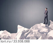 Купить «Thoughtful young businessman standing on a pile of crumpled paper with a grey background», фото № 33938088, снято 7 июля 2020 г. (c) easy Fotostock / Фотобанк Лори