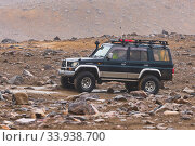 Купить «Japanese SUV Toyota Land Cruiser Prado driving on rocky mountain road on background volcanic landscape. Active vacation, off-road trip in gloomy rainy weather», фото № 33938700, снято 18 августа 2019 г. (c) А. А. Пирагис / Фотобанк Лори