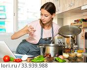 Купить «Girl cooking soup with help of laptop», фото № 33939988, снято 10 июля 2020 г. (c) Яков Филимонов / Фотобанк Лори