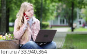 Young blonde girl In Casual Talking Via Mobile Phone And Doing Freelance Work On laptop In A Park on a Sunny summer day. Стоковое видео, видеограф Алексей Кузнецов / Фотобанк Лори