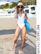 Купить «Sexy girl in swimsuit with bag walking at sea beach», фото № 33941344, снято 10 июля 2018 г. (c) Яков Филимонов / Фотобанк Лори