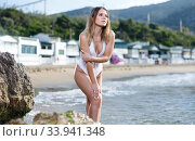 Купить «Young sexy woman in swimsuit posing at sea shore near hotel», фото № 33941348, снято 10 июля 2018 г. (c) Яков Филимонов / Фотобанк Лори