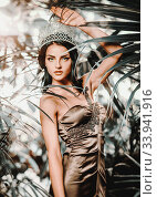 Купить «Gorgeous young 20s woman wearing long evening elegant dress and tiara on head posing surrounded by lush tropical foliage trees. Beauty and fashion concept», фото № 33941916, снято 7 сентября 2014 г. (c) Alexander Tihonovs / Фотобанк Лори