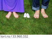 Young Pregnant Couple Feet barefoot on green gras. Стоковое фото, фотограф Nataliia Zhekova / Фотобанк Лори
