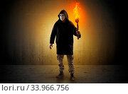 Купить «Ugly scary man with burning flambeau walking in an empty space», фото № 33966756, снято 13 июля 2020 г. (c) easy Fotostock / Фотобанк Лори