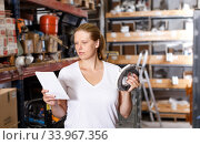 Купить «Female holding shop list and looking tools at shelves in modern build store», фото № 33967356, снято 20 сентября 2018 г. (c) Яков Филимонов / Фотобанк Лори