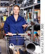 Young woman in uniform looking construction materials with basket in build shop. Стоковое фото, фотограф Яков Филимонов / Фотобанк Лори