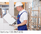 Купить «Builder working with ceramic tiles», фото № 33967616, снято 28 мая 2018 г. (c) Яков Филимонов / Фотобанк Лори