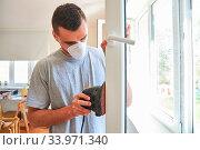 Купить «Mann mit Atemschutzmaske und Schleifmaschine beim Fenster restaurieren und abschleifen», фото № 33971340, снято 3 июля 2020 г. (c) age Fotostock / Фотобанк Лори