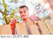 Mann beim Zaun streichen mit Holzfarbe im Garten als Heimwerker. Стоковое фото, фотограф Zoonar.com/Robert Kneschke / age Fotostock / Фотобанк Лори