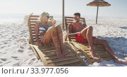 Caucasian couple sitting on sunbeds on the beach. Стоковое видео, агентство Wavebreak Media / Фотобанк Лори