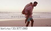 Купить «Caucasian couple enjoying time at the beach», видеоролик № 33977080, снято 25 февраля 2020 г. (c) Wavebreak Media / Фотобанк Лори