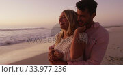Caucasian couple enjoying time at the beach during the sunset. Стоковое видео, агентство Wavebreak Media / Фотобанк Лори