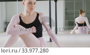 Купить «Caucasian female ballet dancer stretching up on the floor and preparing for dance class», видеоролик № 33977280, снято 24 октября 2019 г. (c) Wavebreak Media / Фотобанк Лори