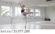 Купить «Caucasian female ballet dancer practicing ballet during a dance class in a bright studio», видеоролик № 33977288, снято 24 октября 2019 г. (c) Wavebreak Media / Фотобанк Лори