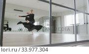 Купить «Caucasian female ballet dancer practicing ballet during a dance class in a bright studio», видеоролик № 33977304, снято 24 октября 2019 г. (c) Wavebreak Media / Фотобанк Лори