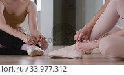 Купить «Caucasian ballet female dancers sitting together on the floor and chatting while tying ballet shoes», видеоролик № 33977312, снято 24 октября 2019 г. (c) Wavebreak Media / Фотобанк Лори