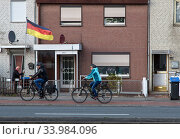 Germany, Bremen - terraced houses in the working class district Groepelingen near the harbour, residents adjust German flag. Редакционное фото, агентство Caro Photoagency / Фотобанк Лори