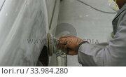 Купить «African American male car mechanic wearing a face mask and polishing a side of a car with a grinder», видеоролик № 33984280, снято 6 ноября 2019 г. (c) Wavebreak Media / Фотобанк Лори
