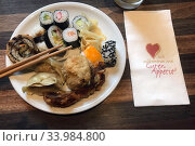 Berlin, Germany, Sushi, ginger and dim sum on a plate next to a napkin (2020 год). Редакционное фото, агентство Caro Photoagency / Фотобанк Лори