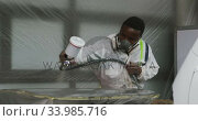 Купить «African American male car mechanic with a suit and painting a piece of a car with a spraying gun », видеоролик № 33985716, снято 6 ноября 2019 г. (c) Wavebreak Media / Фотобанк Лори