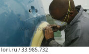 African American male car mechanic wearing a face mask and using a polisher on the side of a car. Стоковое видео, агентство Wavebreak Media / Фотобанк Лори