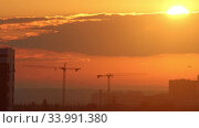 High crane works on building site while the orange sunset. Стоковое видео, видеограф Константин Шишкин / Фотобанк Лори
