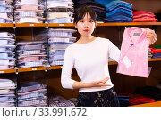 Купить «Chinese female shopping assistant offering various shirt in men's cloths store», фото № 33991672, снято 7 июля 2020 г. (c) Яков Филимонов / Фотобанк Лори
